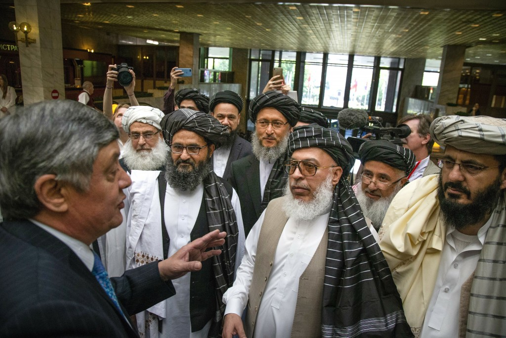 FILE - In this file photo taken on Tuesday, May 28, 2019, Russian presidential envoy to Afghanistan Zamir Kabulov, left, speaks to Mullah Abdul Ghani ...