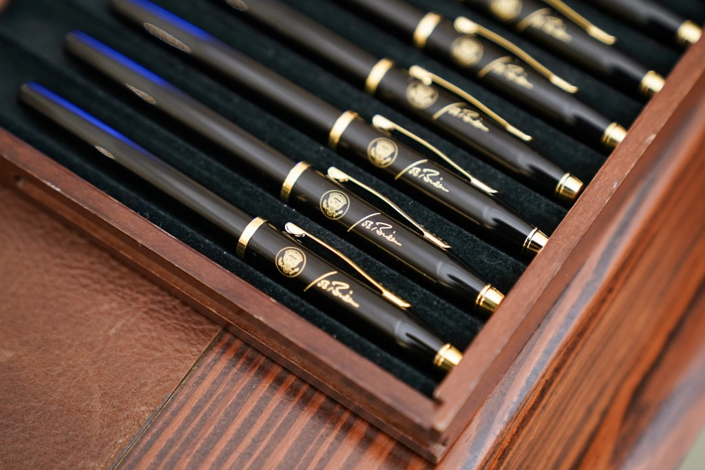 FILE - In this Jan. 21, 2021, file photo pens featuring President Joe Biden's signature and presidential seal, are displayed in the State Dinning Room...