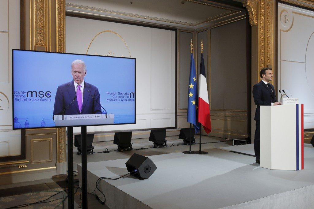French President Emmanuel Macron, right, attends a video-conference meeting as U.S. President Joe Biden appear on a screen ahead of a 2021 Munich Secu...