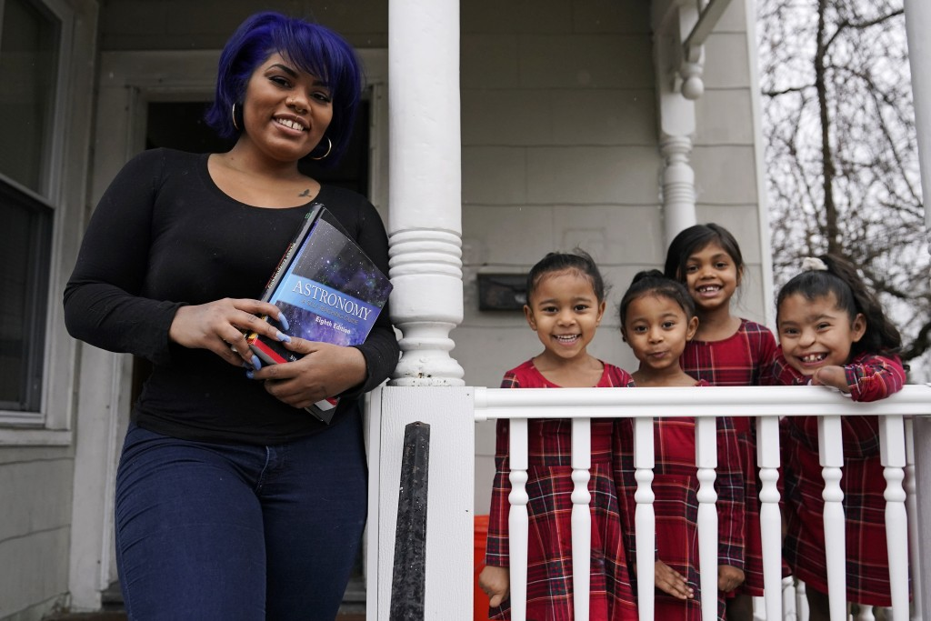Dinora Torres, a MassBay Community College student, poses with her four daughters on the front porch of their home, Thursday, Jan. 14, 2021, in Milfor...
