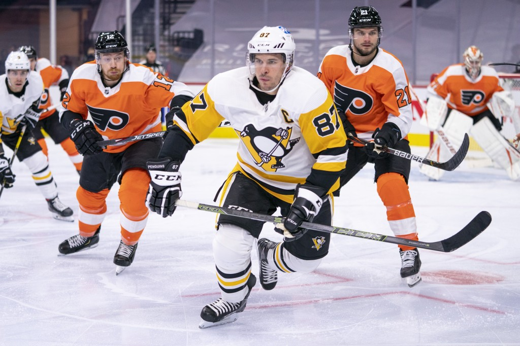 FILE - Pittsburgh Penguins' Sidney Crosby, center, heads after the puck after winning the face off against Philadelphia Flyers' Scott Laughton, right,...