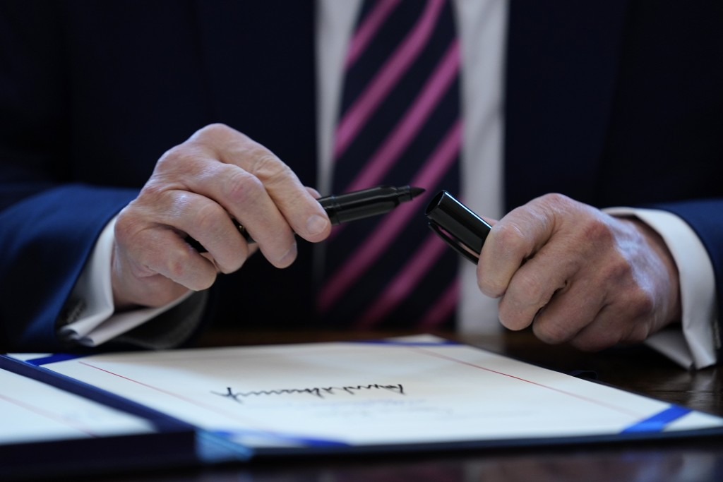 FILE - In this April 24, 2020, file photo President Donald Trump puts the cap on a pen after signing a coronavirus aid package to direct funds to smal...
