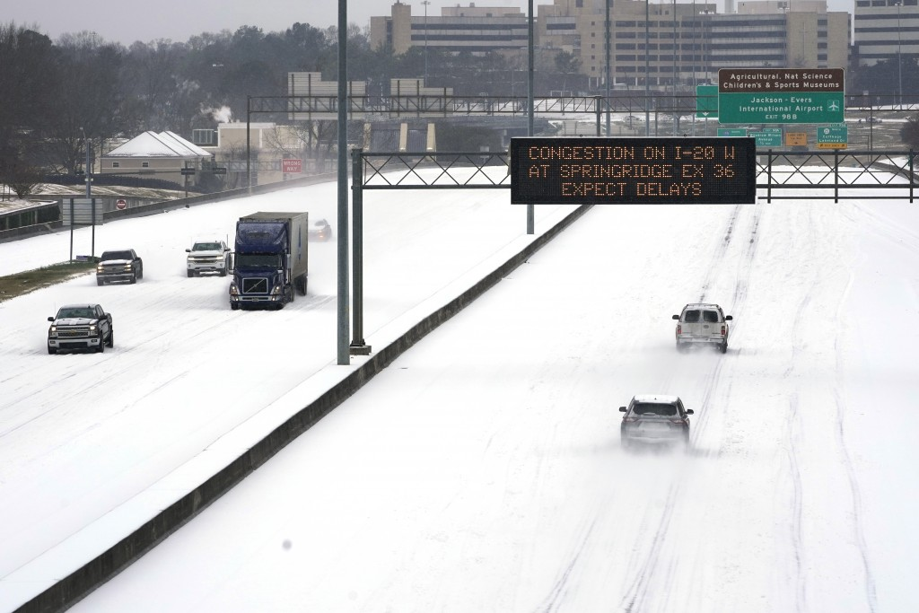 FILE - In this Feb. 15, 2021, file photo, an electronic message board advises drivers of potential congestion as they drive over snow on Interstate 55...