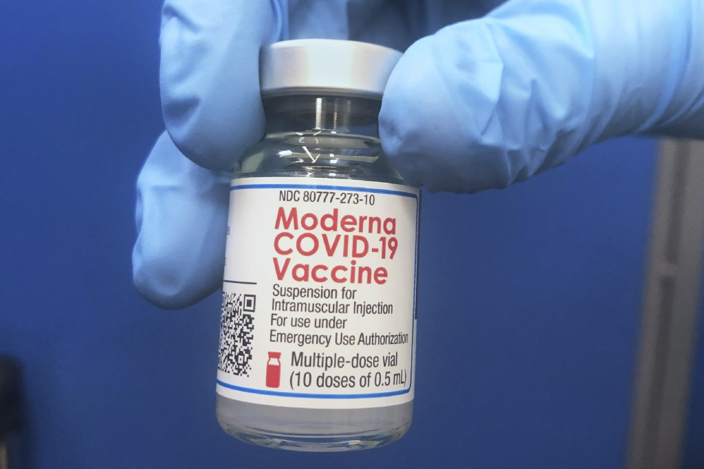 A vial of Moderna COVID-19 vaccine is held at a vaccination site Friday, Feb. 19, 2021, in Oklahoma City. (AP Photo/Sue Ogrocki)