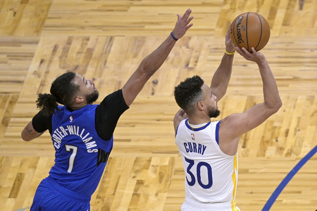 Golden State Warriors guard Stephen Curry (30) goes up for a shot in front of Orlando Magic guard Michael Carter-Williams (7) during the first half of...