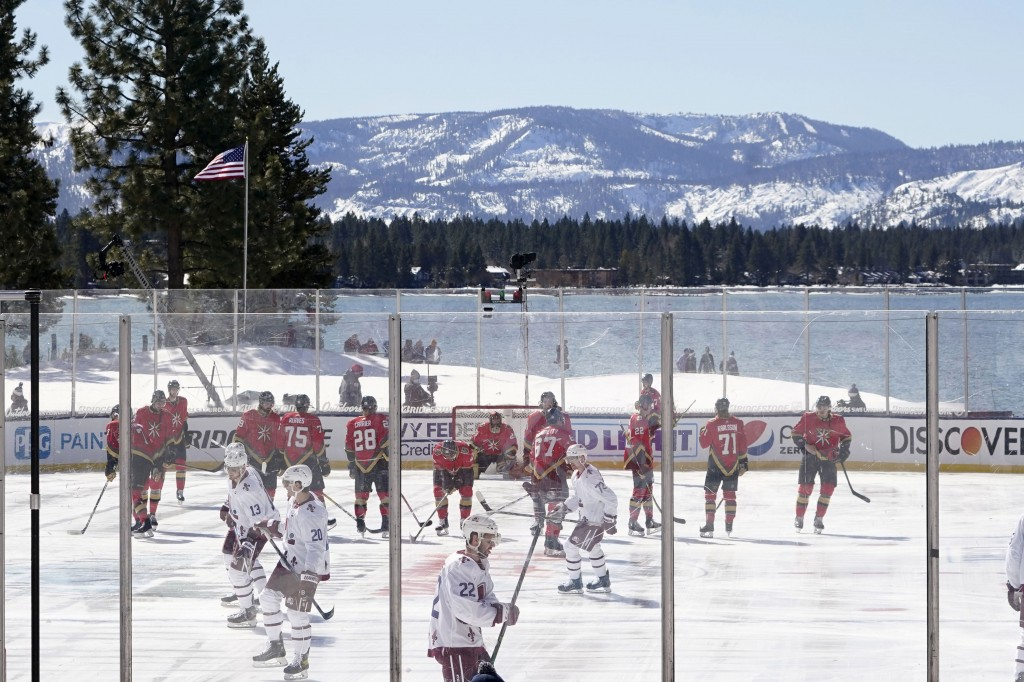 Members of the Colorado Avalanche, in white, and the Vegas Golden Knights, red, prepare to face off to start the first period of the Outdoor Lake Taho...