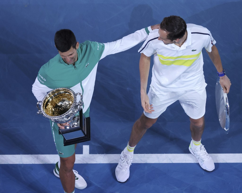 Serbia's Novak Djokovic, left, and Russia's Daniil Medvedev talk after receiving their trophies after Djokovic won the men's singles final at the Aust...