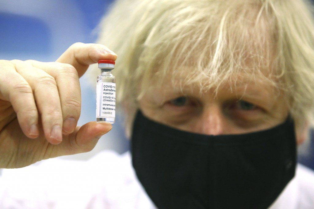 FILE - In this Wednesday, Feb. 17, 2021 file photo, Britain's Prime Minister Boris Johnson holds a vial of the Oxford/Astra Zeneca Covid-19 vaccine at...