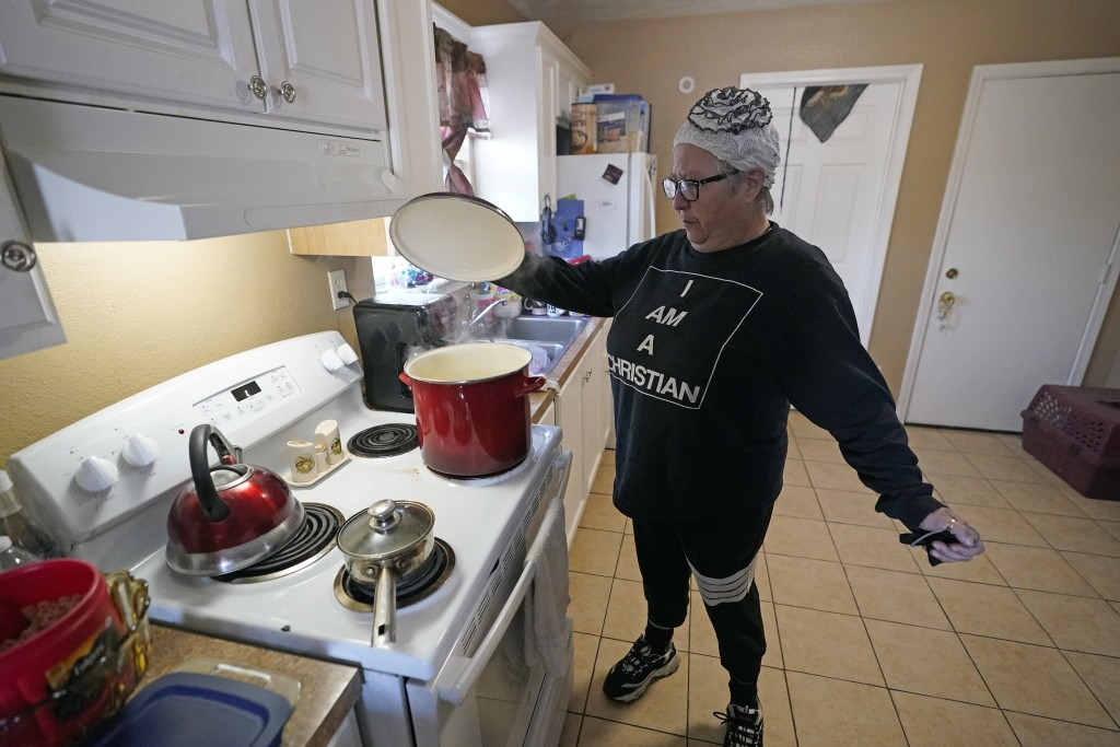FILE - In this Feb. 19, 2021, file photo, Nancy Wilson boils water in her home in Houston. She does not have full running water as the city remains un...
