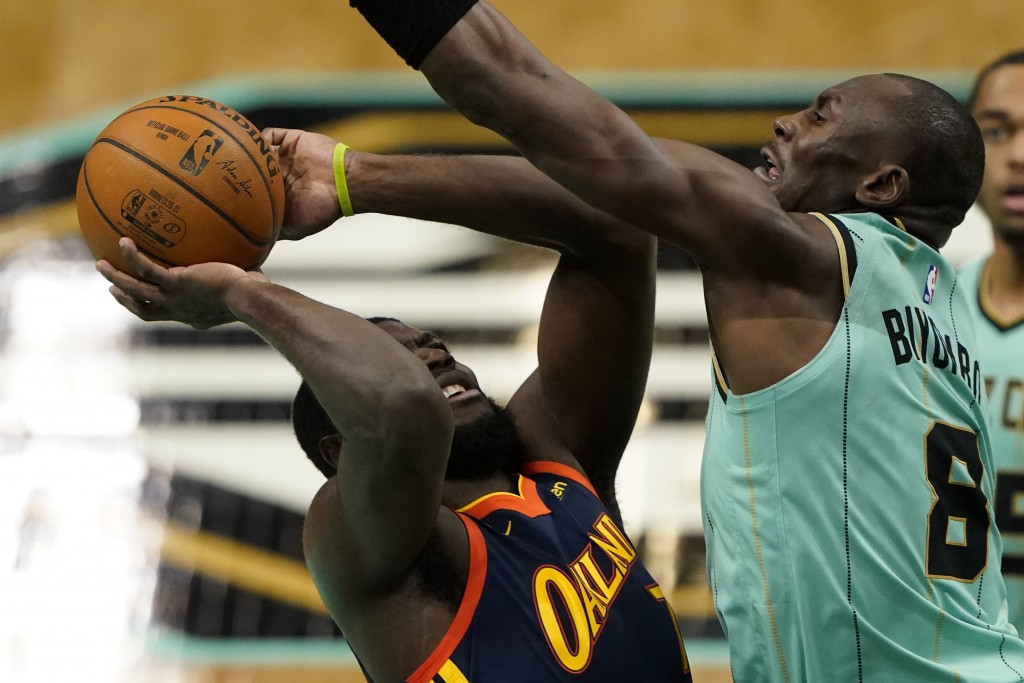 Charlotte Hornets center Bismack Biyombo, right, guards Golden State Warriors' Eric Paschall during the first half of an NBA basketball game on Saturd...