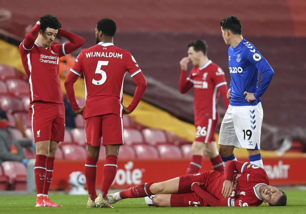 Liverpool's Jordan Henderson lies injured on the ground during the English Premier League soccer match between Liverpool and Everton at Anfield in Liv...
