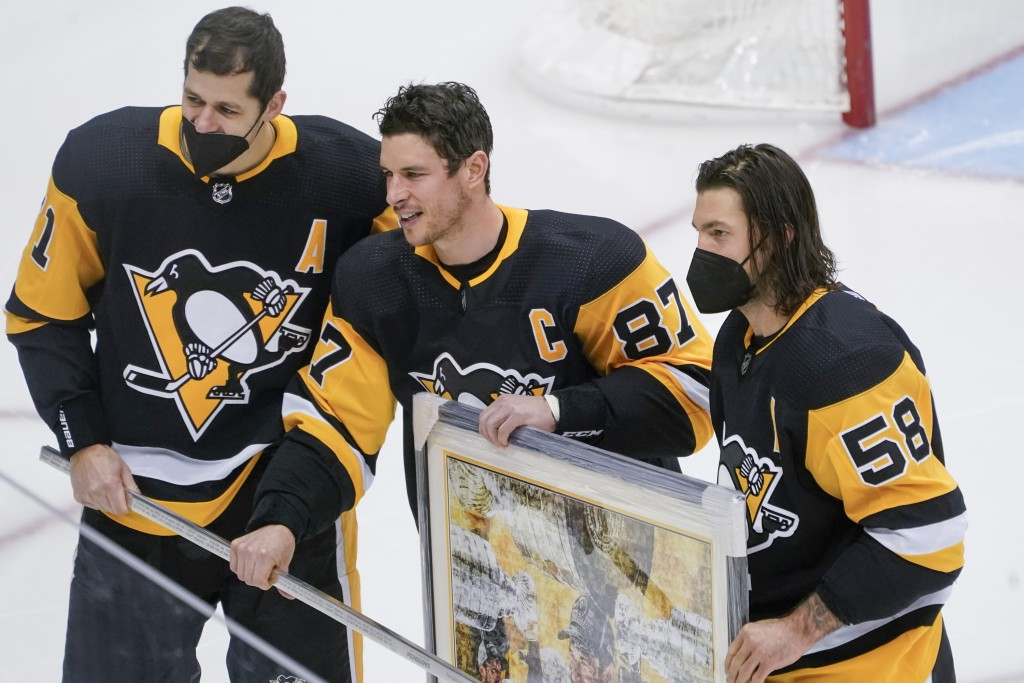 Pittsburgh Penguins' Sidney Crosby, center, poses with Evgeni Malkin, left, and Kris Letang during a ceremony honoring his 1000th NHL hockey game with...
