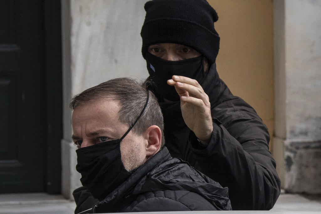 A plain clothed policeman escorts handcuffed actor and director Dimitris Lignadis, as he leaves a magistrate's office in Athens, Sunday, Feb. 21, 2021...