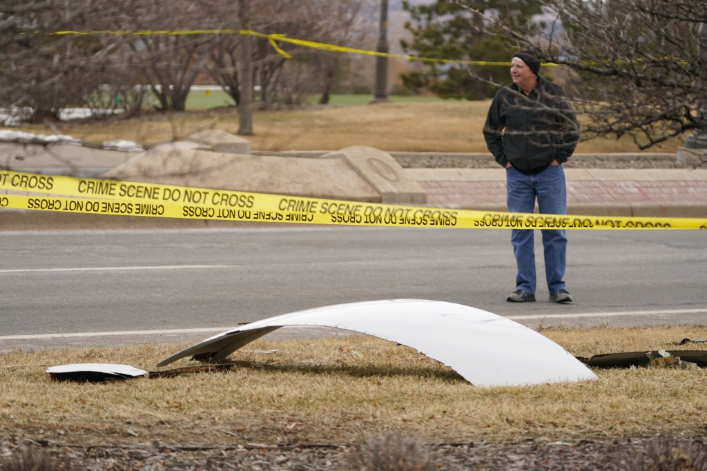 A piece of debris from a commercial airplane is surrounded by police tape on a strip along Midway Boulevard in Broomfield, Colo., after the plane shed...
