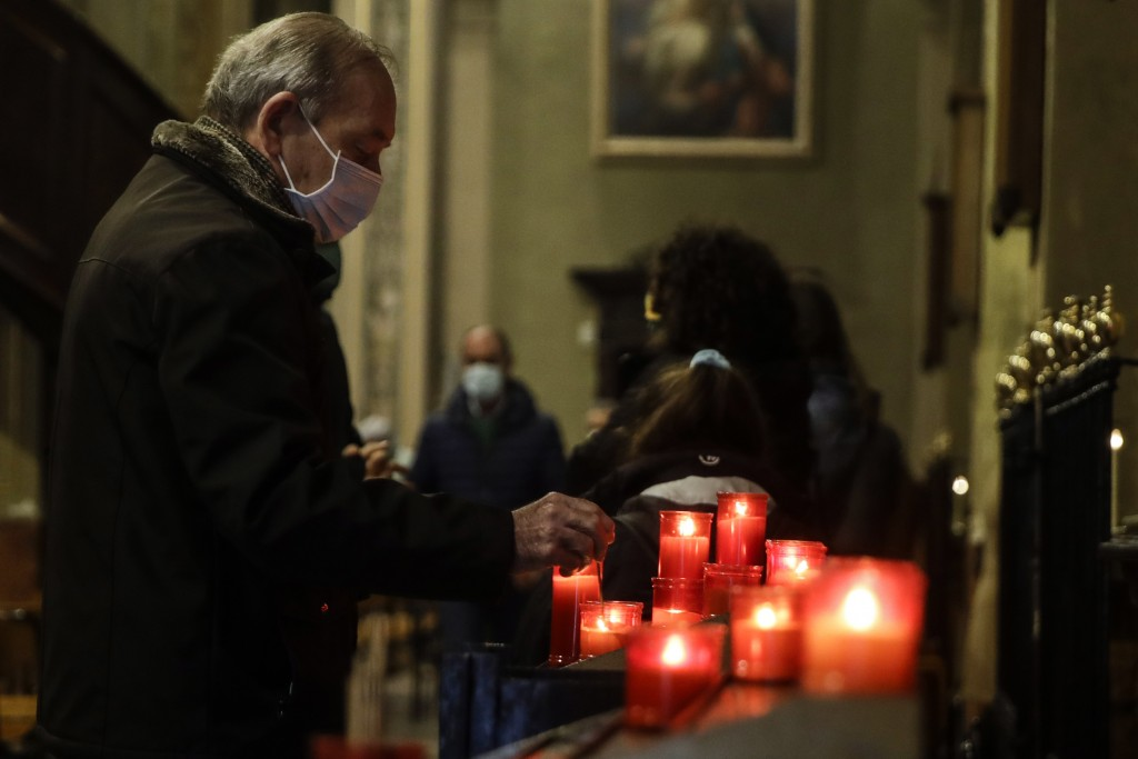 A man lights a candle during a Mass at the San Biagio church in Codogno, northern Italy, Sunday, Feb. 21, 2021. The first case of locally spread COVID...