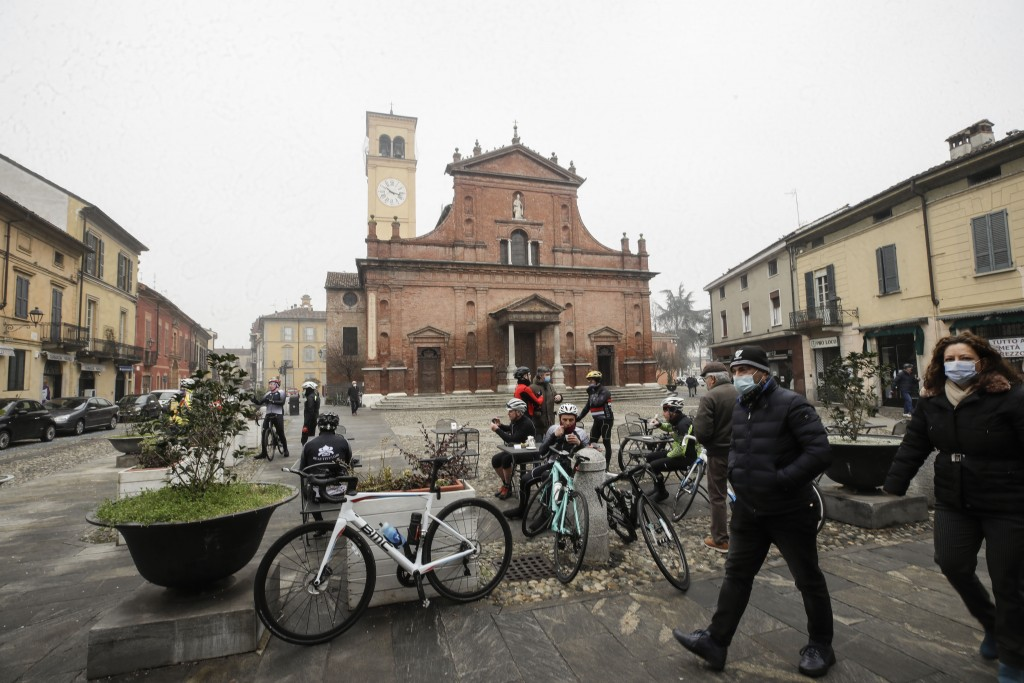 People and cyclists relax in front of the San Biagio church in Codogno, northern Italy, Sunday, Feb. 21, 2021. The first case of locally spread COVID-...