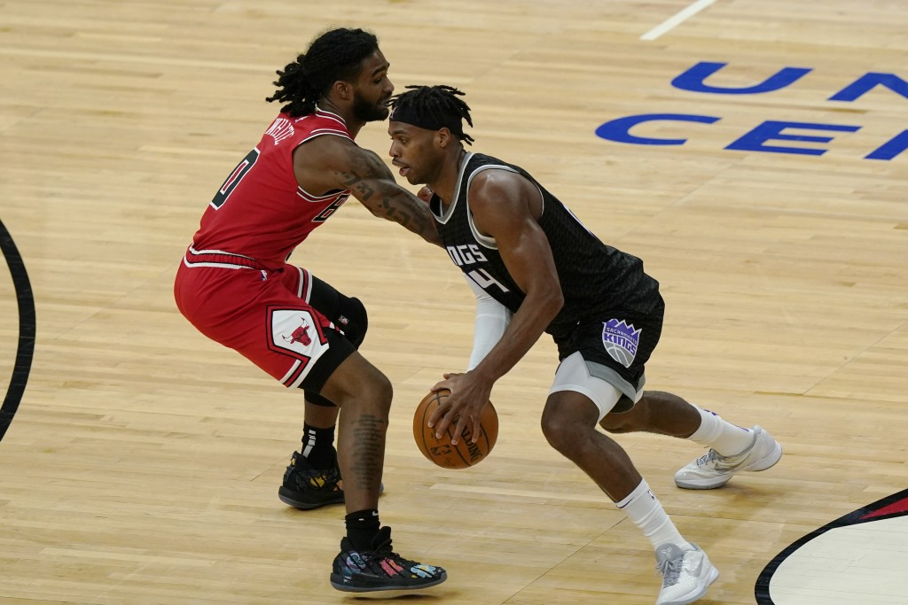 Sacramento Kings guard Buddy Hield, right, drives against Chicago Bulls guard Coby White during the first half of an NBA basketball game in Chicago, S...