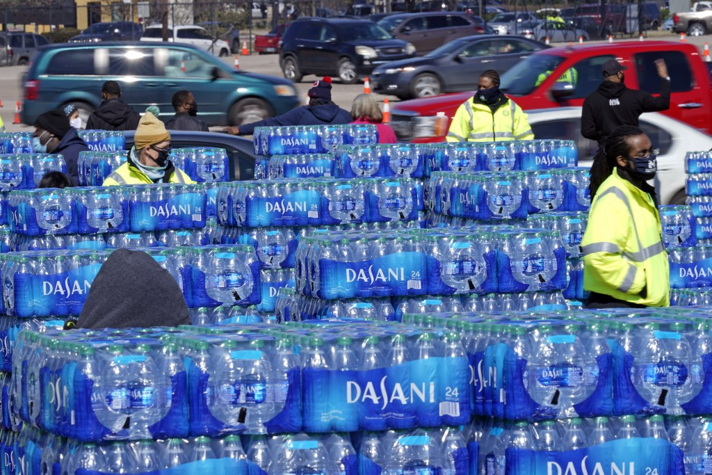 FILE - In this Feb. 19, 2021, file photo, water is loaded into cars at a City of Houston water distribution site in Houston. The drive-thru stadium lo...