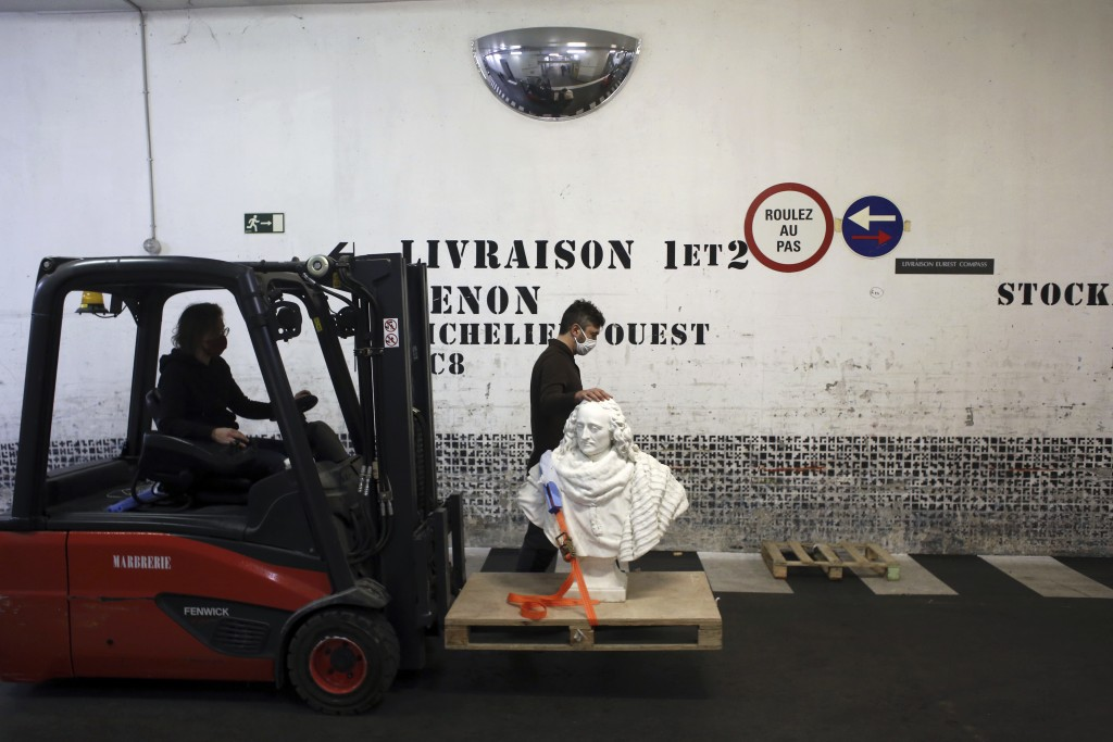 Workers transport a bust of Guillaume de Lamoignon by French sculptor Francois Girardon, in the Louvre museum, in Paris, Wednesday, Feb. 17, 2021. The...