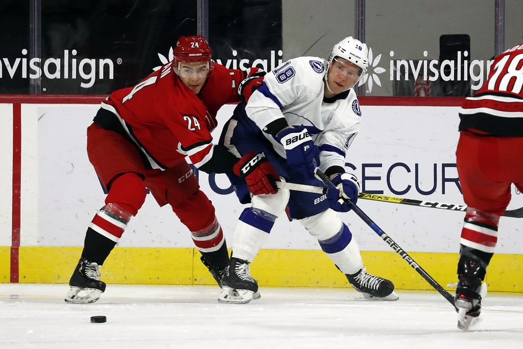 Tampa Bay Lightning's Ondrej Palat (18) passes the puck when challenged by Carolina Hurricanes' Jake Bean (24) during the second period of an NHL hock...