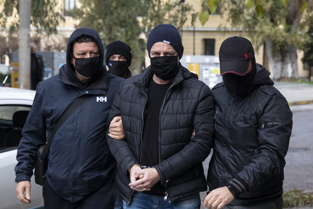 Plain-clothed policemen escort handcuffed well-known actor and director Dimitris Lignadis, center, to a magistrate's office in Athens, Sunday, Feb. 21...