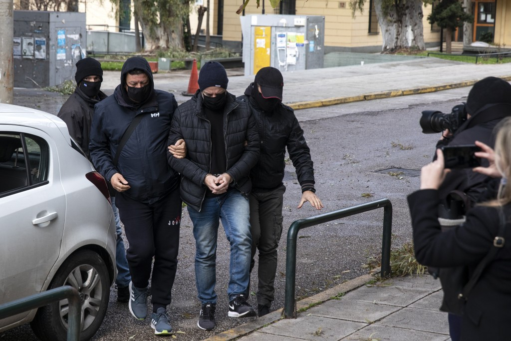 Plain-clothed policemen escort handcuffed well-known actor and director Dimitris Lignadis to a magistrate's office in Athens, Sunday, Feb. 21, 2021. L...