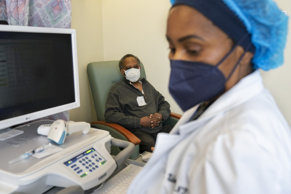 In this Wednesday, Feb. 10, 2021, photo the Rev. James Coleman, 70, waits as his COVID-19 vaccine is prepared by nurse practitioner Ifreke Udodong, at...