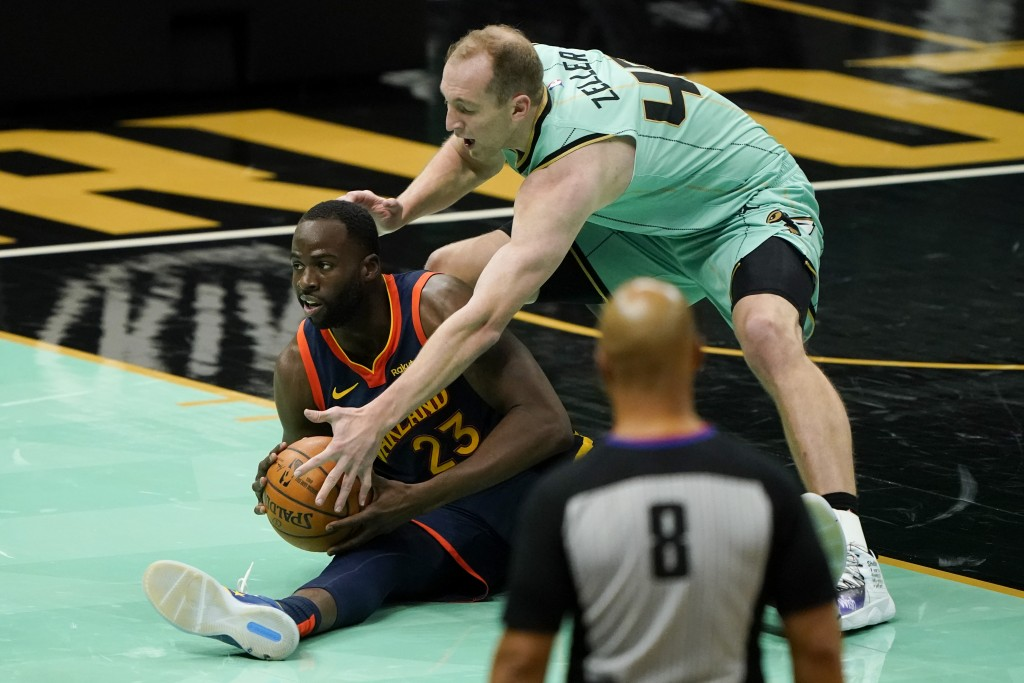 Golden State Warriors forward Draymond Green (23) and Charlotte Hornets center Cody Zeller battle for a loose ball during the second half of an NBA ba...