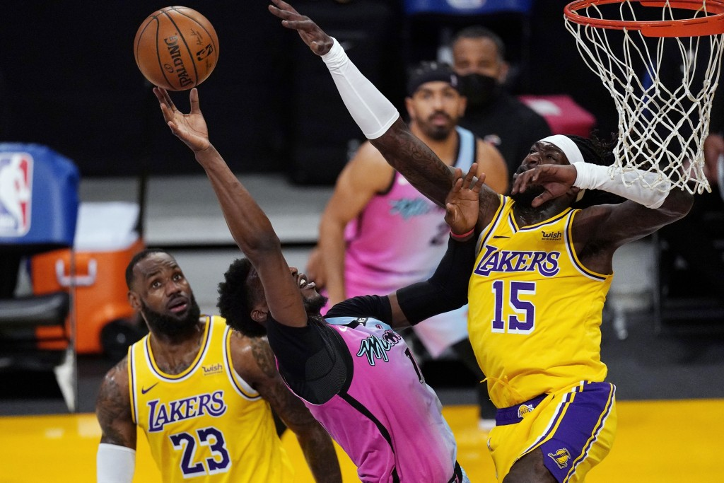 Miami Heat center Bam Adebayo, center, shoots as Los Angeles Lakers forward LeBron James, left, and center Montrezl Harrell defend during the first ha...