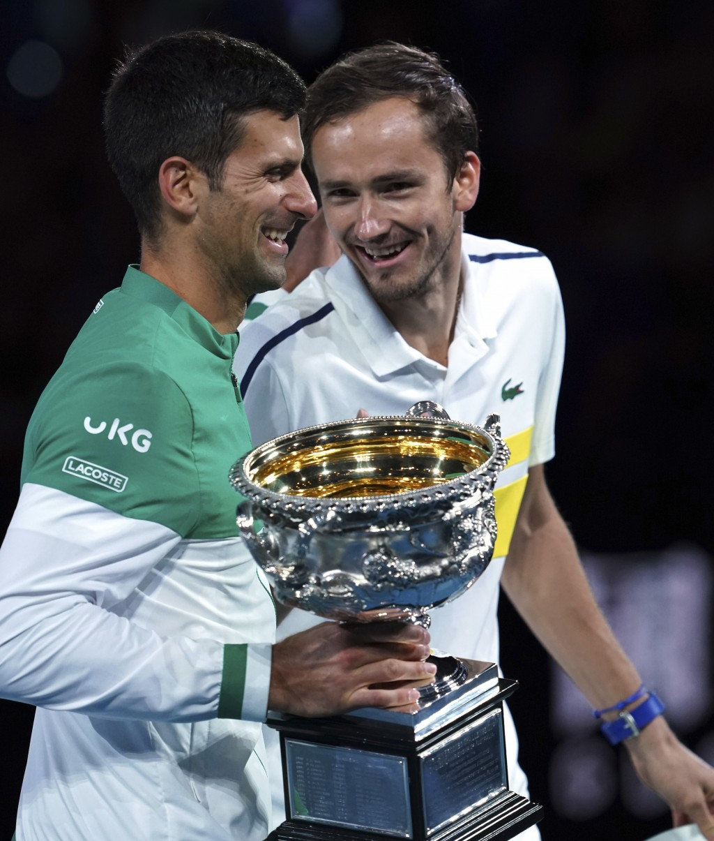 Serbia's Novak Djokovic, left, holds the Norman Brookes Challenge Cup as he talks with runner-up Russia's Daniil Medvedev after winning the men's sing...