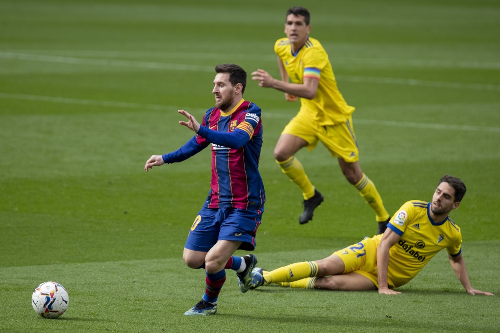 Barcelona's Lionel Messi, left, controls the ball during the Spanish La Liga soccer match between FC Barcelona and Cadiz at the Camp Nou stadium in Ba...