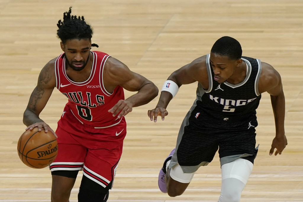 Chicago Bulls guard Coby White, left, drives against Sacramento Kings guard De'Aaron Fox during the first half of an NBA basketball game in Chicago, S...