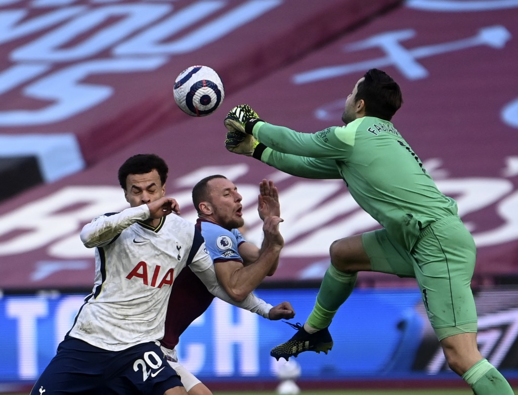 West Ham's goalkeeper Lukasz Fabianski, right, makes a save in front of Tottenham's Dele Alli, left, during the English Premier League soccer match be...