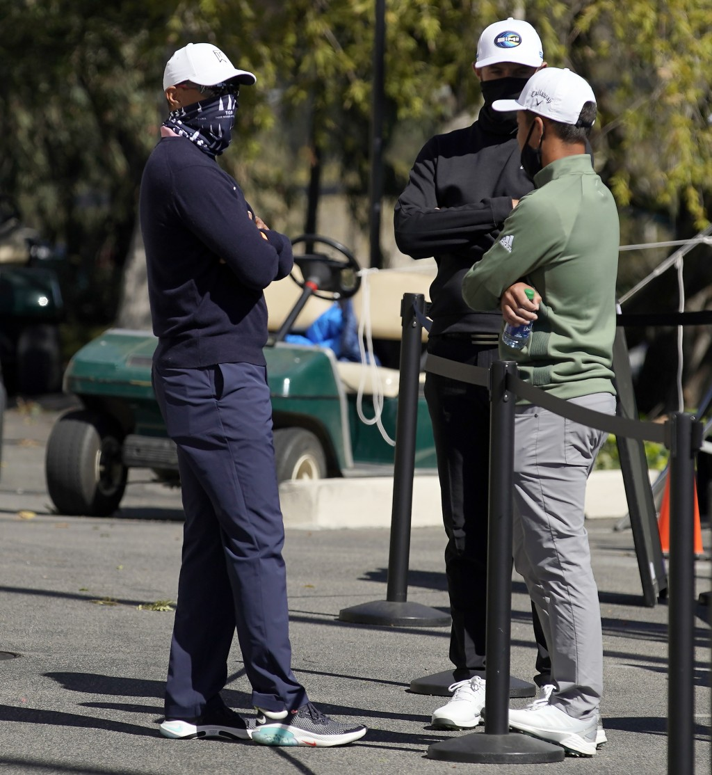 From left, Tiger Woods, Dustin Johnson and Xander Schauffele talk after high winds suspended play during the third round of the Genesis Invitational g...