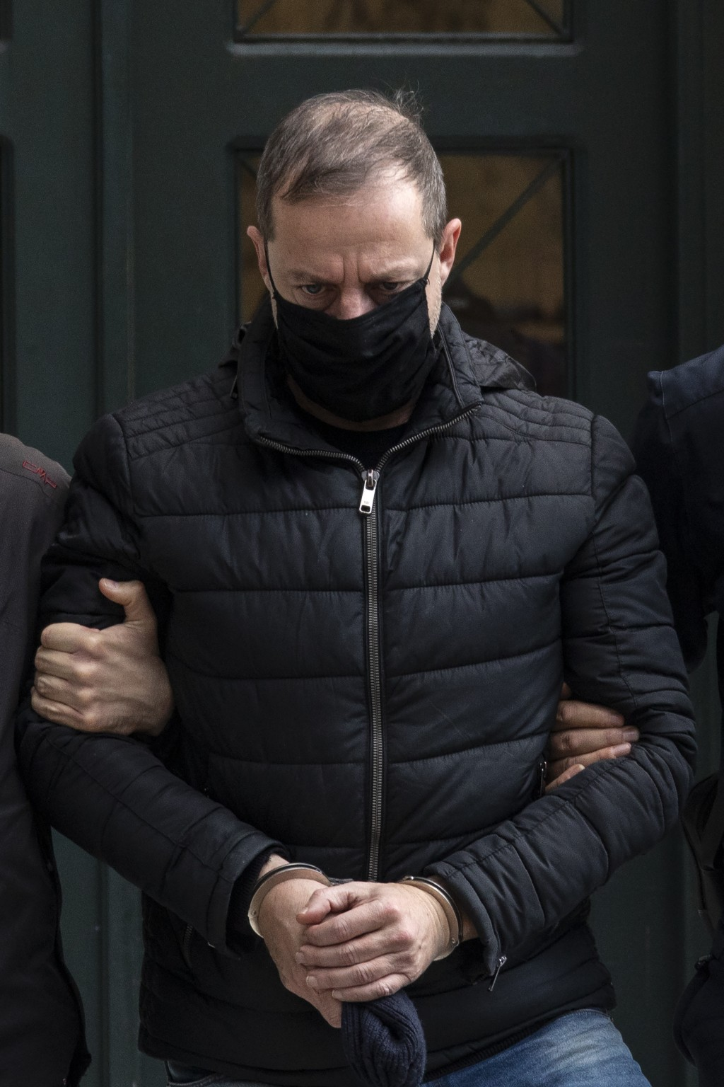 Handcuffed actor and director Dimitris Lignadis, leaves a magistrate's office in Athens, Sunday, Feb. 21, 2021. Lignadis, 56, the former artistic dire...