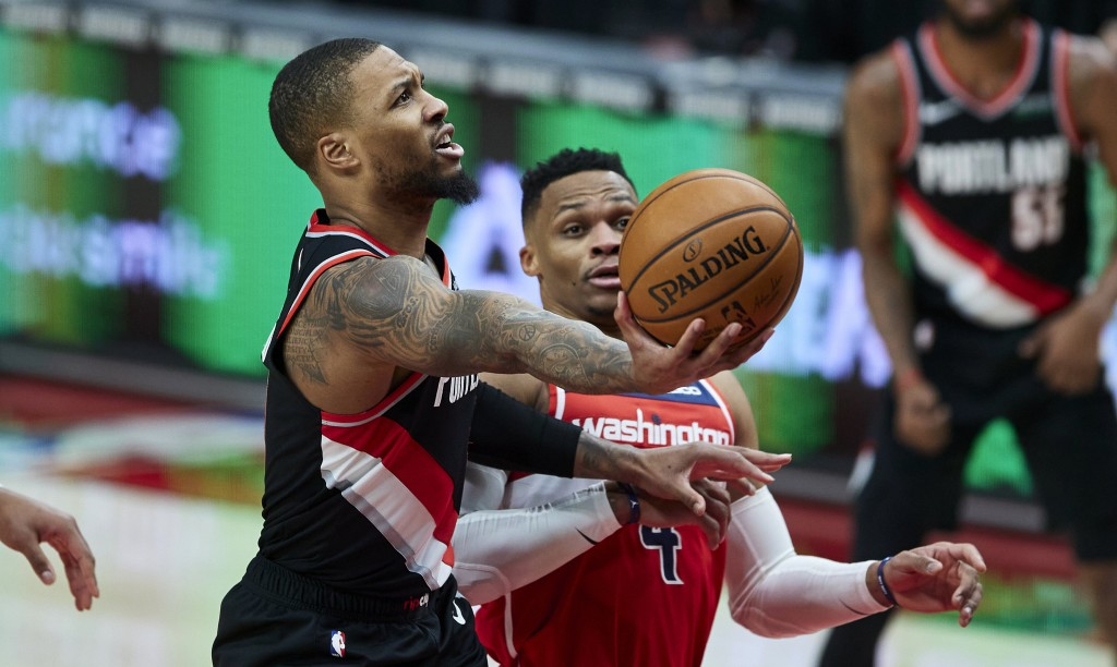 Portland Trail Blazers guard Damian Lillard, left, shoots next to Washington Wizards guard Russell Westbrook during the second half of an NBA basketba...
