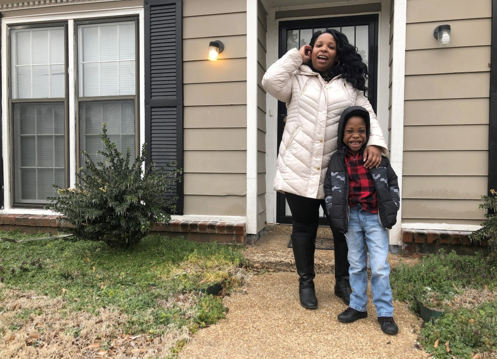 Leah Williamson, left, and her 7-year-old son Carpenter Adoo pose for a photo in front of their house on Saturday, Feb. 13, 2021, in Memphis, Tenn. Ca...