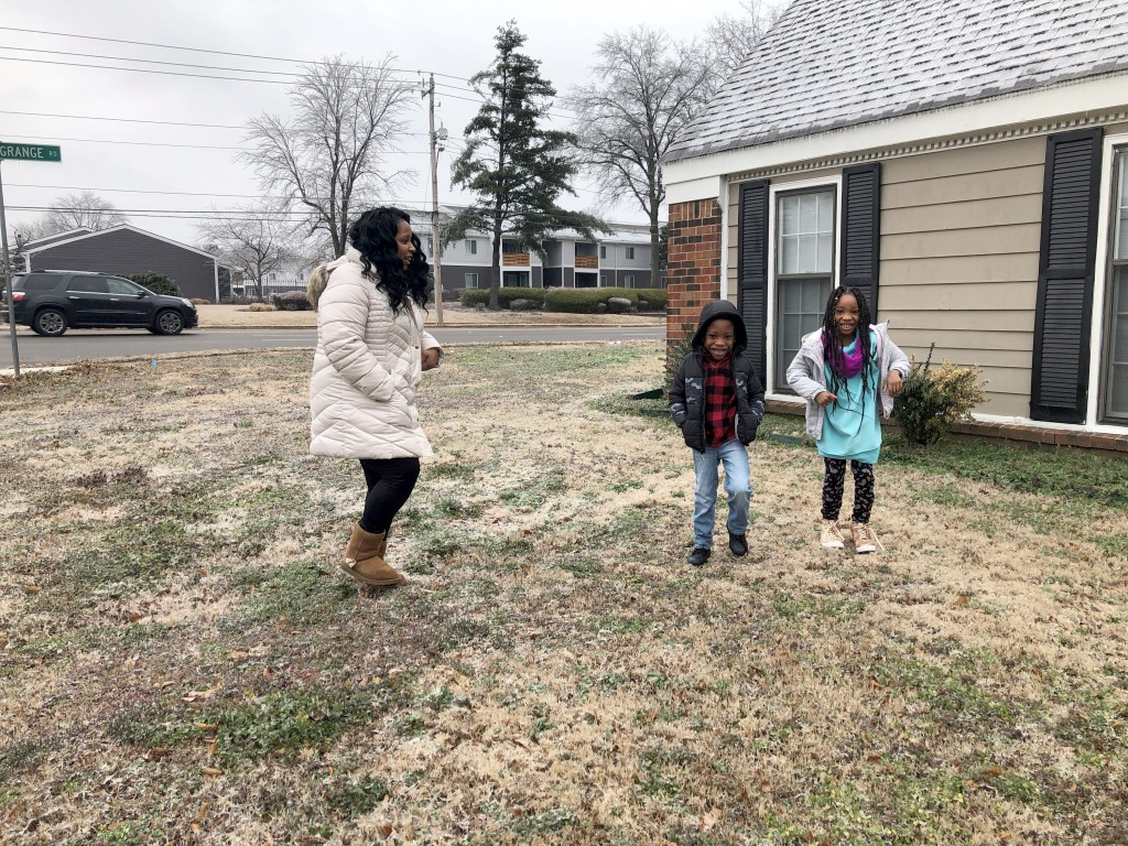 Leah Williamson, left, and her twin 7-year-old children Carpenter Adoo, center, and Sira Joy Adoo jump on the icy, frozen ground outside their home on...