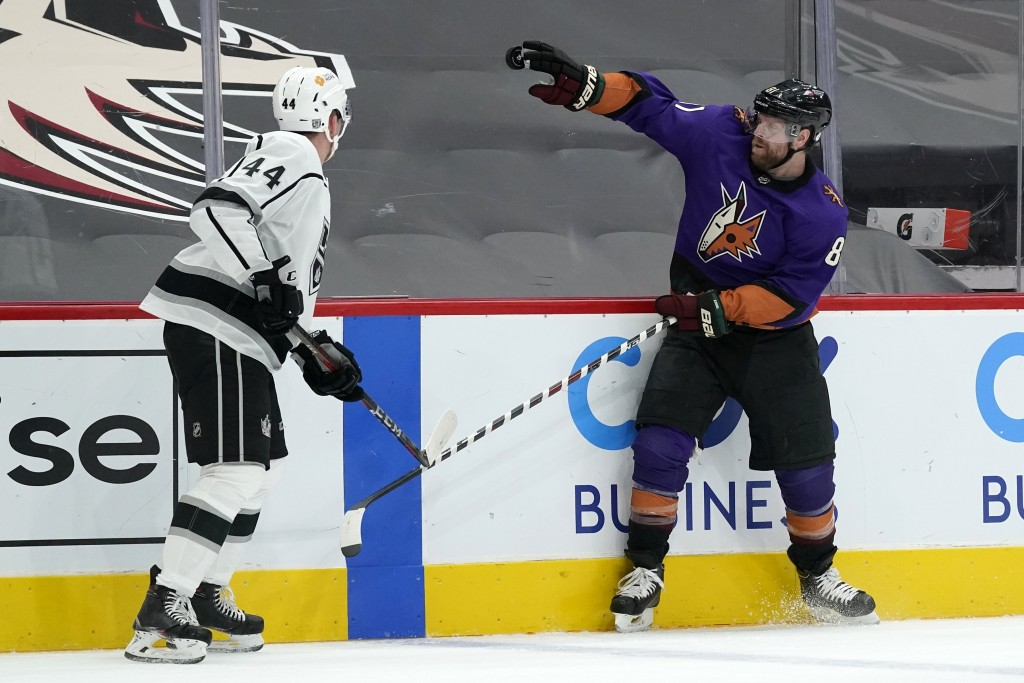 Arizona Coyotes right wing Phil Kessel (81) knocks the puck down with his glove as Los Angeles Kings defenseman Mikey Anderson (44) looks on during th...