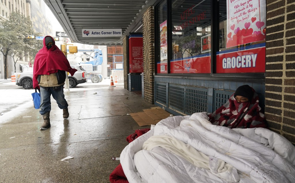 FILE - In this Feb. 18, 2021, file photo, a woman living on the streets uses blankets to keep warm in downtown San Antonio. Snow, ice and sub-freezing...