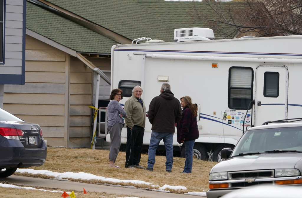 Neighbors gather on the lawn next to the home of Kirby Klements after a piece of debris crushed the man's pickup truck parked next to his home in Broo...