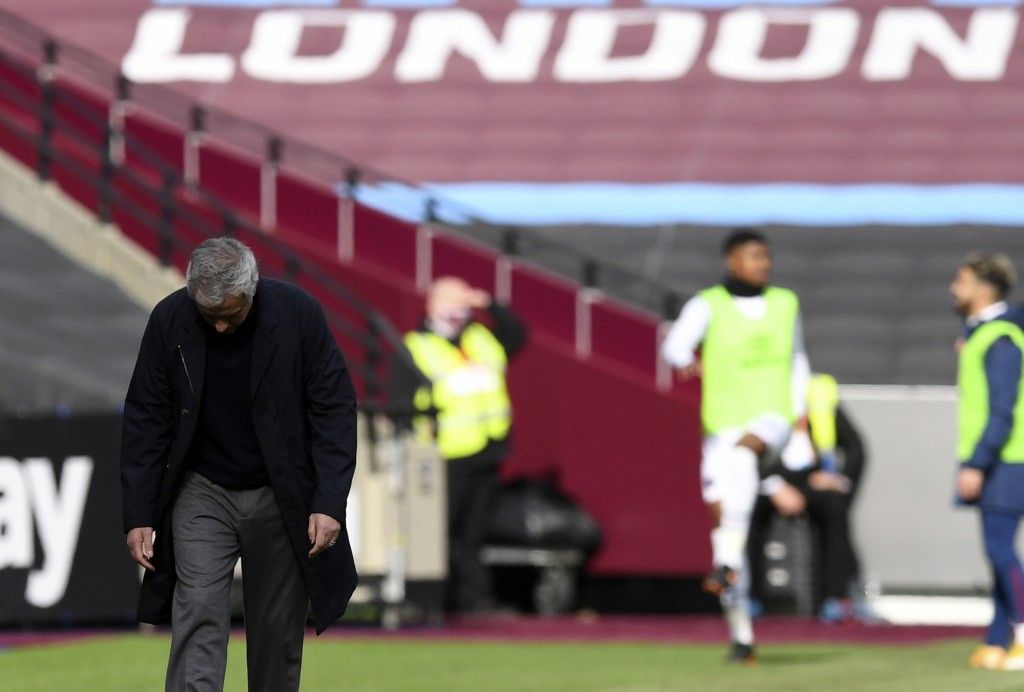 Tottenham's manager Jose Mourinho, left, reacts during the English Premier League soccer match between West Ham United and Tottenham at the London Sta...