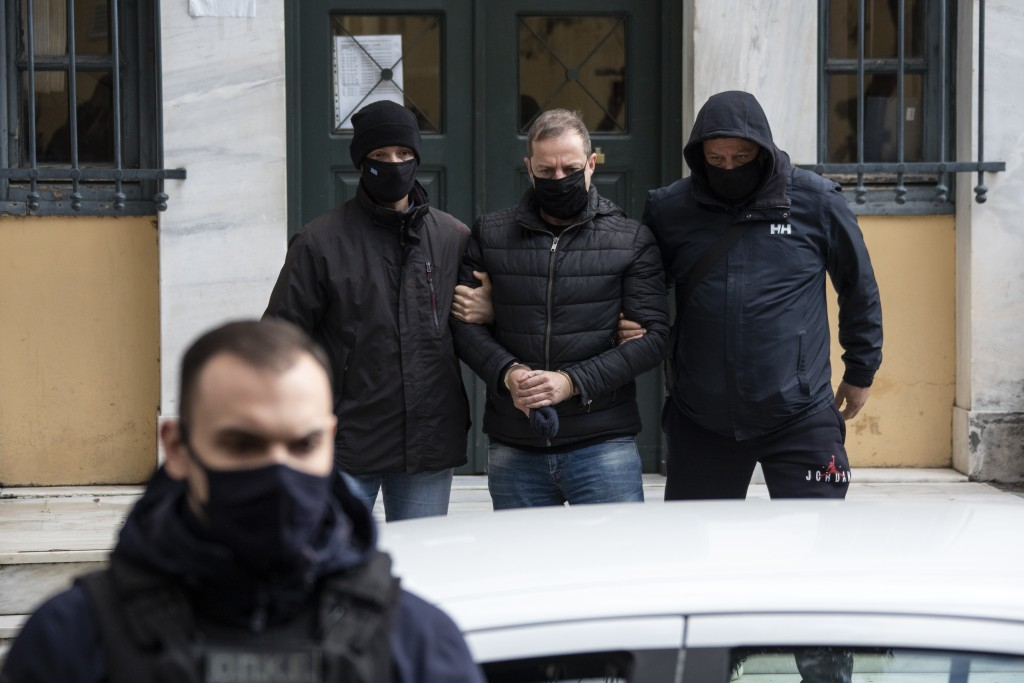 Plain clothed police officers escort handcuffed well-known actor and director Dimitris Lignadis, center, as they leave a magistrate's office in Athens...