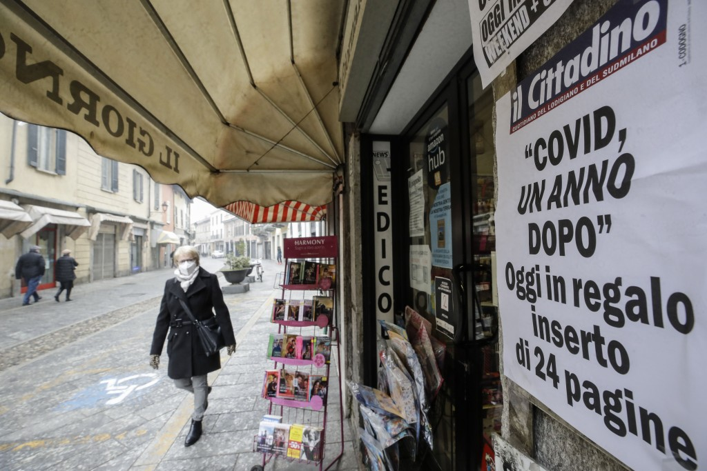 """A woman walks past a newsstand with the local paper headline reading """"Covid, One Year After"""", in Codogno, northern Italy, Sunday, Feb. 21, 2021. The f..."""