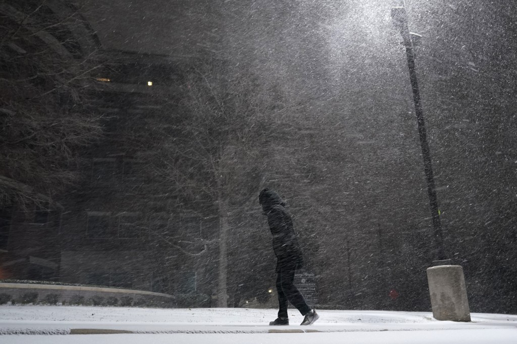 FILE - In this Feb. 14, 2021, file photo, woman walks through falling snow in San Antonio. As temperatures plunged and snow and ice whipped the state,...