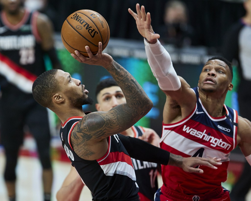 Portland Trail Blazers guard Damian Lillard, left, shoots as Washington Wizards guard Russell Westbrook defends during the second half of an NBA baske...