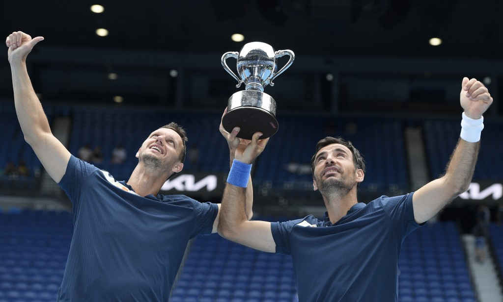 Croatia's Ivan Dodig, right, and Slovakia's Filip Polasek hold their trophy aloft after defeating Rajeev Ram of the US and Britain's Joe Salisbury in ...