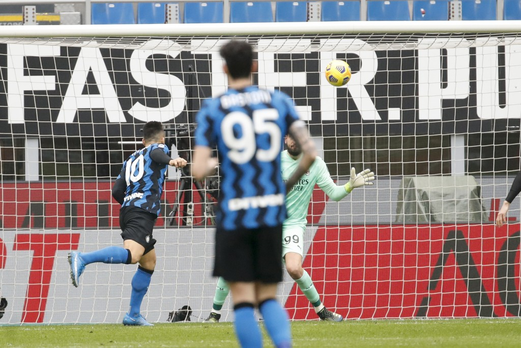 Inter Milan's Lautaro Martinez, left, scores his side's opening goal during the Serie A soccer match between AC Milan and Inter Milan, at the Milan Sa...