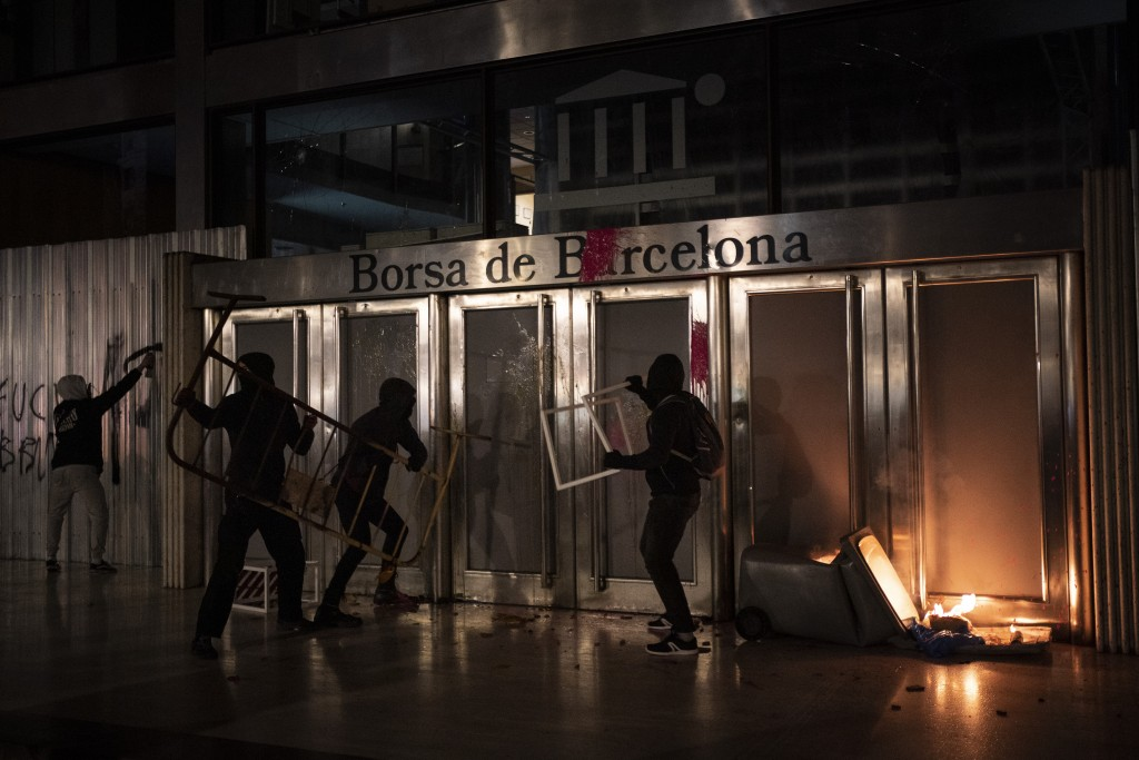 Demonstrators damage the Barcelona Stock Exchange building during a protest condemning the arrest of rap singer Pablo Hasél in Barcelona, Spain, Satur...