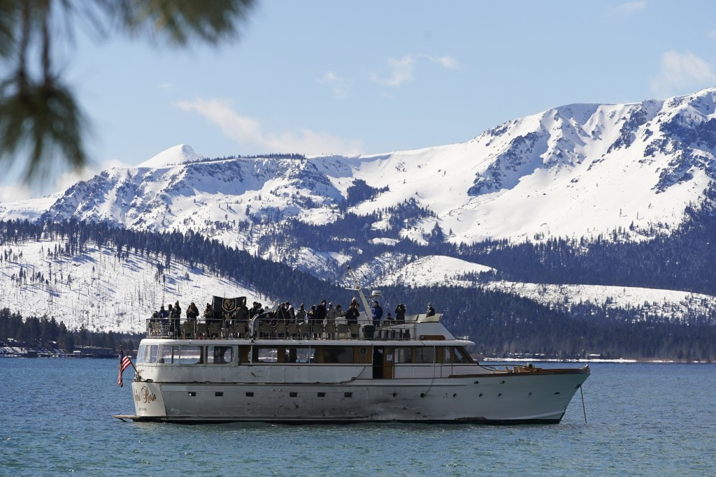 A flag of the Vegas Golden Knights is displayed on a boat floating on Lake Tahoe off shore of the temporary ice rink where the Golden Knights will pla...
